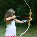 girl shooting archery bow and arrow