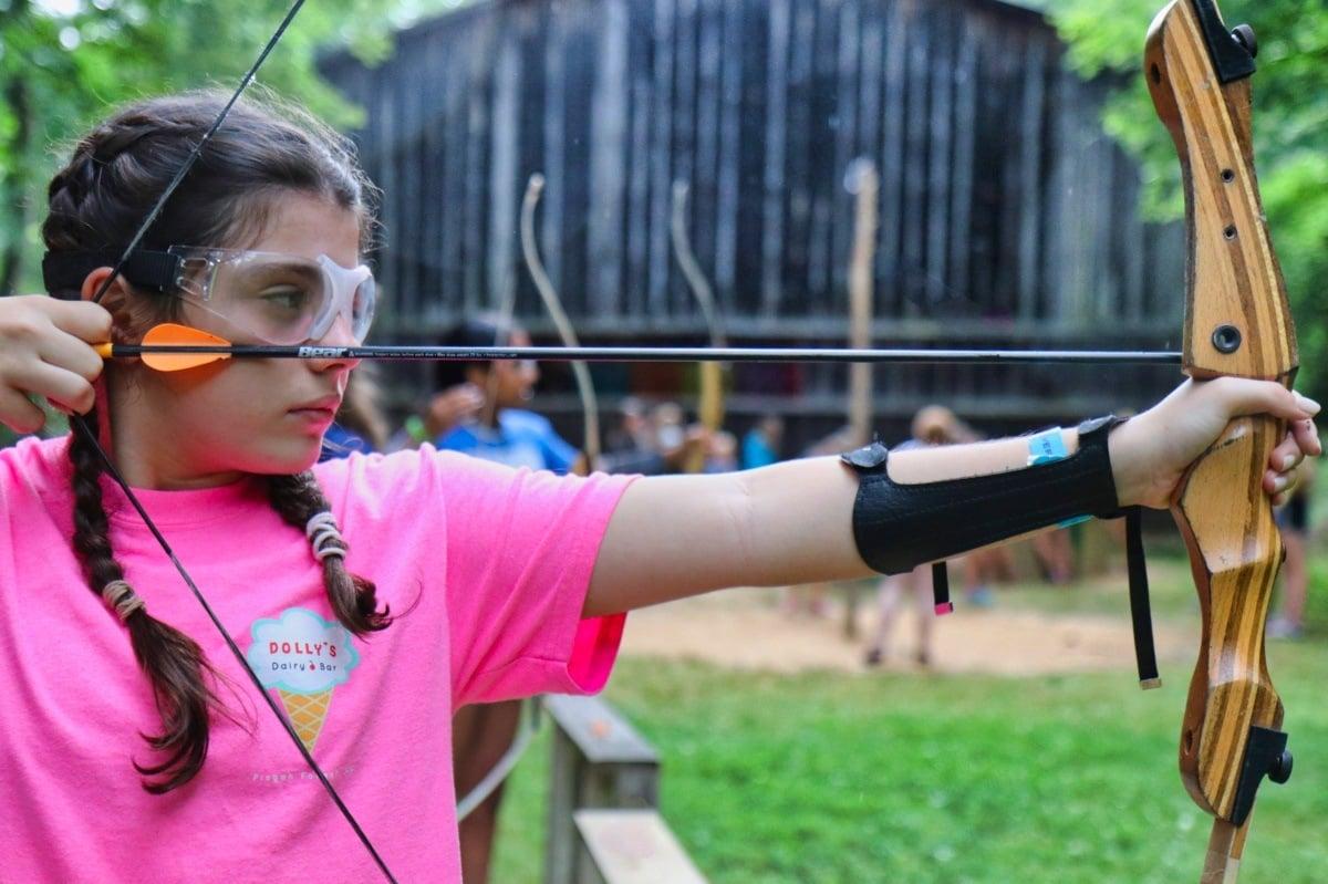 Camp girl aiming arrow