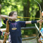 Kids learning archery at summer camps