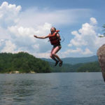 Cmapers jumping off rock into the lake