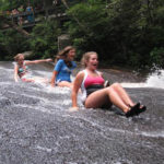 Camp girls sliding down the rock in the water