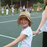 Child enjoying a square dance with neighboring camp