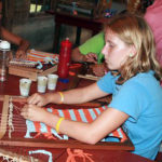 Camp girls weaving on hand loom