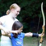 girl summer camp archery teaching