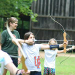 Kids shooting archery at summer camps