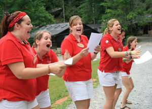 Counselors leading songs at camp assembly