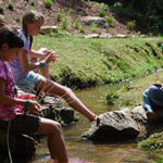 Girls weaving baskets by the creek