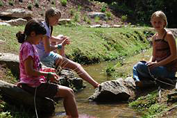 Girls weaving baskets by the creek