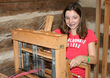 camp kid weaving on the loom