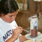 Camp girls painting ceramics pieces