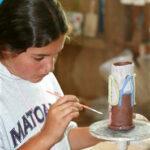 Camp girls painting ceramics pieces
