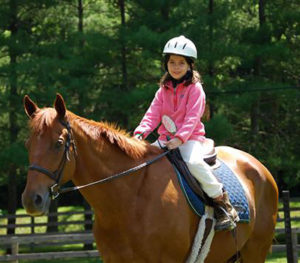 Camp girl horseback riding