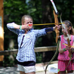 Kid shooting archery at summer camp