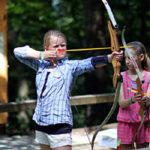 Kid shooting archery at summer camp