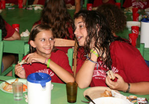 summer camper and counselor at dinner