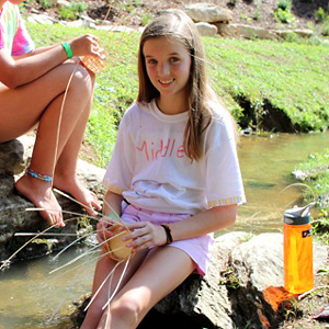 Camp girls making a baskets in the creek