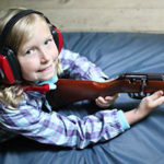 Little girl camper ready to shoot rifle