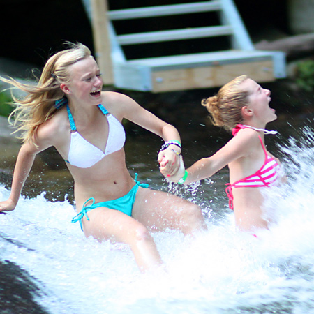 girls splashing into sliding rock pool