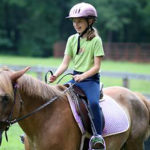 smiling camp girl horseback riding