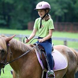 smiling camp girl horseback riding