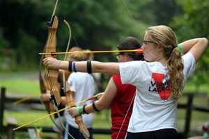 Camp kid shooting archery bow and arrow