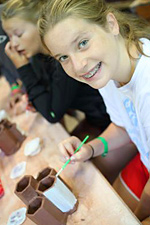 kid making ceramics in camp pottery class