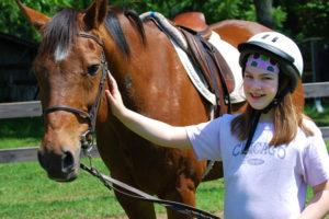Camper girl gently caring for her horse