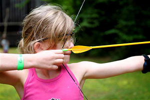 Camp girl pulling archery bow back