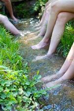 Camp girls soaking their feet in the creek