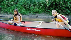 Camp girls canoeing on river