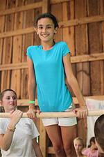 Camp girl balancing on gymnastics high bar