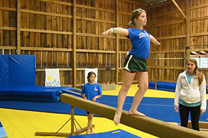 Camp child doing gymnastics on balance beam