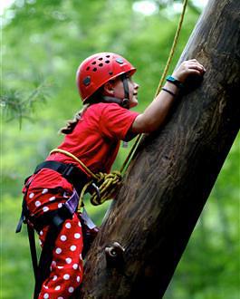 Camp girls climbing tower wearing polka dot pants