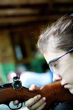 Camp girl aiming her rifle
