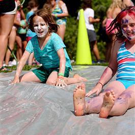 camp girls enjoying slip n slide