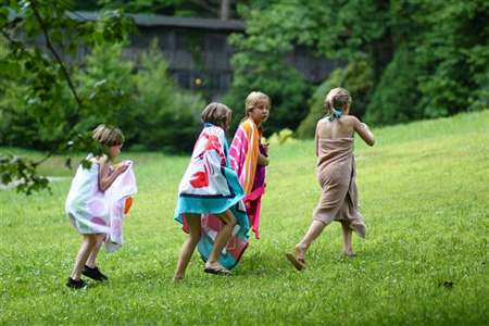 Camper girls walking up grassy hill