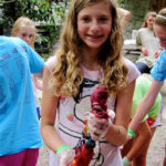 Camp child making tie dye t-shirt