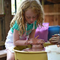 Camp girl throwing pot on ceramics wheel