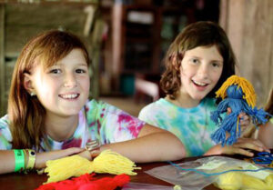 Girls making a yard doll at camp
