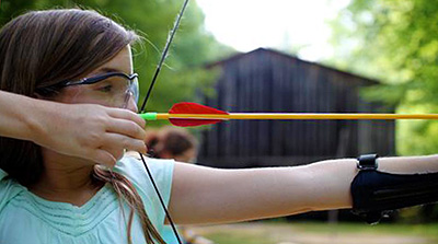 Girl pauses pulling archery bow
