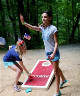 Camp girls play corn hole game