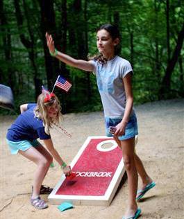 Camp girls play corn hole game