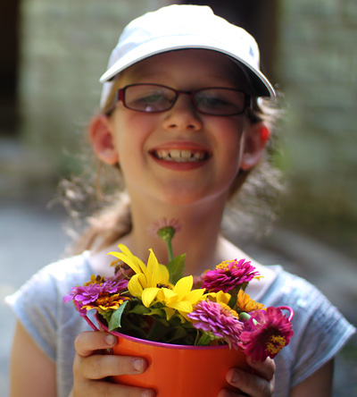 Young girl holding pot of cut flowers