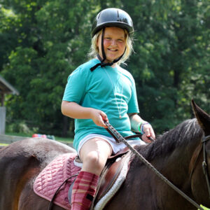 Young camper kid horseback riding