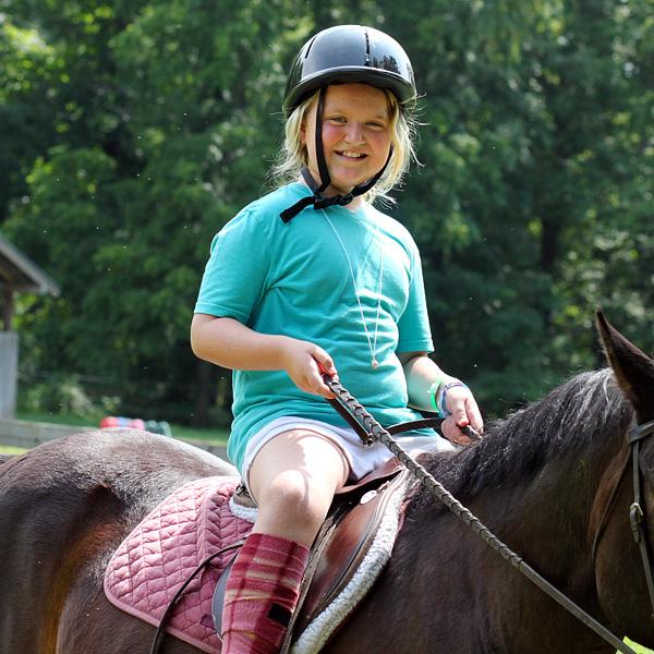 Young camper kid horseback riding