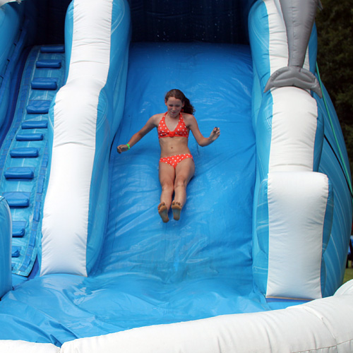 Camp girl slides down inflated slide