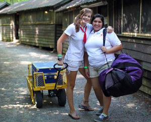 Two camper girls moving luggage
