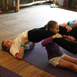 camp kids doing partner yoga pose