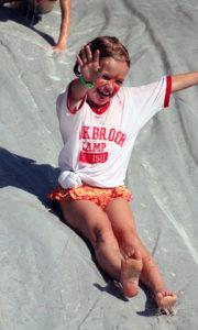 Girl summer camp enjoys slip slide