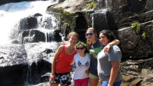 Camp girls hike near waterfall